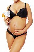 Tanned pregnant women holding pills