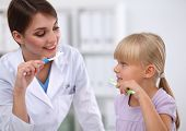 Dentist and little girl in the dentist office.isolated