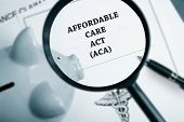 stock photo of policy  - Magnifying glass over Affordable Care Act policy and piggy bank - JPG