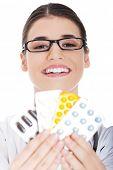 Happy female doctor holding pills