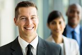 handsome businessman with business team on background