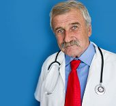 Senior doctor in studio on blue wall