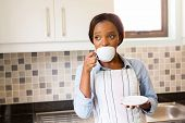 thoughtful african woman drinking coffee at home