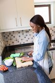 happy african woman chopping vegetables in the kitchen
