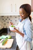 happy african housewife eating green salad in the kitchen