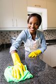 beautiful african woman cleaning the counter in the kitchen