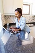 modern african woman using laptop in the kitchen