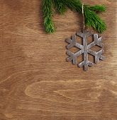 christmas wooden background with snowflake hanging on fir branch