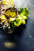 Glass of white wine on dark background