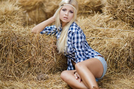 stock photo of shepherdess  - Sexy fashion woman in cow girl country style on hay stack - JPG