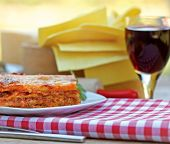stock photo of lasagna  - Lasagna and red wine perfect meal on table - JPG
