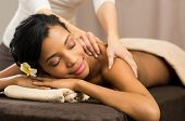 pic of massage oil  - Closeup of happy african woman receiving back massage at salon spa