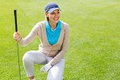stock photo of knee-cap  - Female golfer kneeing on the putting green on a sunny day at the golf course - JPG