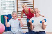 picture of senior class  - Portrait of happy female trainer with senior couple in fitness studio - JPG