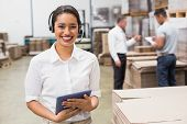 picture of warehouse  - Warehouse manager wearing headset holding clipboard in a large warehouse - JPG