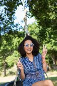 image of tire swing  - Pretty young woman in tire swing on a summers day - JPG