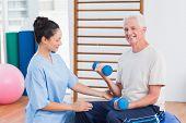 stock photo of senior class  - Female instructor assisting senior man in lifting dumbbells at gym - JPG