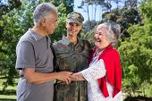 picture of reunited  - Soldier reunited with her parents on a sunny day - JPG