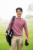 stock photo of golf bag  - Golfer standing holding his golf bag smiling at camera at the golf course - JPG