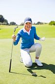 stock photo of ladies golf  - Excited lady golfer cheering on putting green on a sunny day at the golf course - JPG