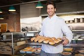 foto of trays  - Happy baker showing tray with bread at the bakery - JPG