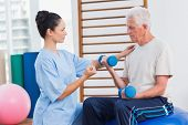 pic of senior class  - Female trainer assisting senior man in lifting dumbbells at gym - JPG