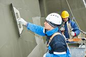 image of putty  - builders at facade plastering work during industrial building with putty knife float - JPG
