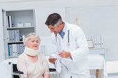 foto of neck brace  - Male doctor writing prescription for patient wearing neck brace in clinic - JPG