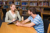 foto of tutor  - Student getting help from tutor in library at the university - JPG