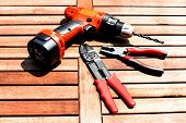 picture of stripper  - Background image of drill driver wire stripper and pliers on the wood table - JPG