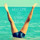 stock photo of spring break  - the text welcome to spring break written on a blurred image of a young man upside down into the sea - JPG