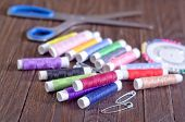 foto of rayon  - color threads and scissors on the wooden table - JPG