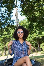 pic of tire swing  - Pretty young woman in tire swing on a summers day - JPG