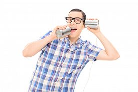 stock photo of tin man  - Silly man talking to himself through tin can phone isolated on white background - JPG