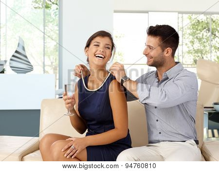 Happy caucasian woman with champagne in hand getting pearl necklace gift from husband. Happy couple,