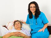 pic of nurse  - Smiling nurse caring for kind elder patient in nursing home.
