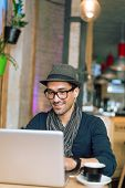 picture of internet-cafe  - Fashionable and stylish young man relaxing with coffee music and internet browsing at the cafe bar - JPG