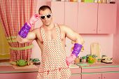 pic of apron  - Handsome muscular man in an apron cooking in the pink kitchen - JPG