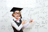 foto of schoolgirls  - Happy smart schoolgirl in big glasses and academic hat performs the task at the blackboard - JPG