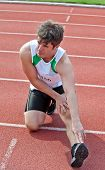 Young Male Sprinter Streching On The Floor Before A Race In A Stadium
