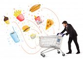 picture of junk  - Businessman pushing a shopping cart and toxic junk food and cigarettes coming out of it - JPG