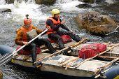 stock photo of raft  - Two men on a makeshift catamaran raft on the northern river - JPG