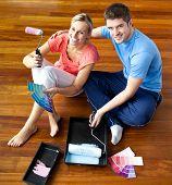 Jovem casal sentado no chão sorrindo