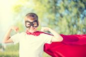 stock photo of little boy  - Superhero Kid Showing his Muscles over nature background - JPG