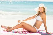 image of sun-tanned  - Pretty blonde woman putting sun tan lotion on her leg at the beach - JPG