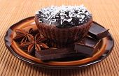 image of chocolate muffin  - Homemade delicious fresh baked chocolate muffins with desiccated coconut pieces of chocolate and star anise lying on plate - JPG