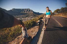 foto of pov  - Fit young woman standing with man stretching his leg outdoors on country road - JPG