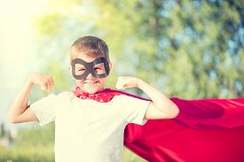 stock photo of muscle  - Superhero Kid Showing his Muscles over nature background - JPG