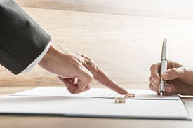 stock photo of divorce-papers  - Male hand pushing a wedding ring over to a female hand about to sign divorce papers - JPG