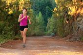 Female athlete running on forest road - copy space. Chinese Asian / Caucasian female woman runner.